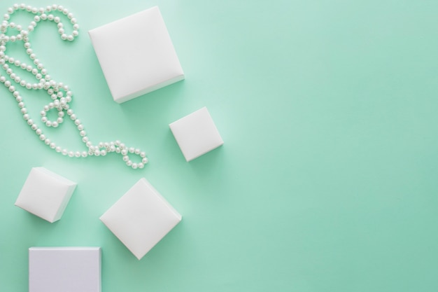 White pearl necklace with variety of white boxes on pale green paper background Free Photo