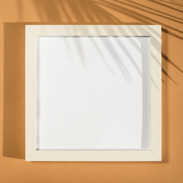 White photo frame on a beige background with a palm leaf shadow Free Photo