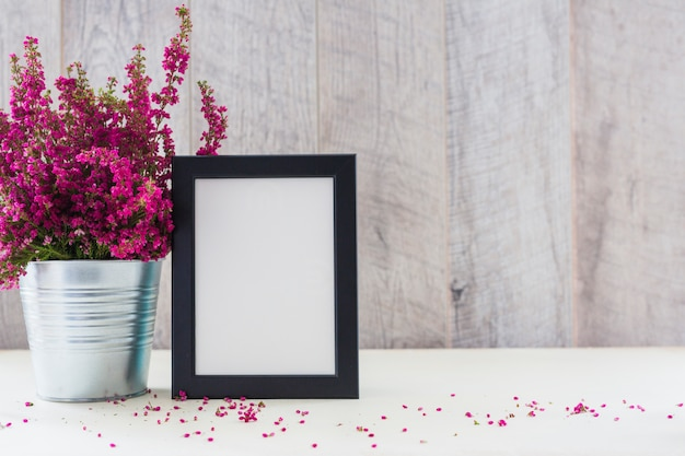 White photo frame and pink flowers in an aluminum pot on desk Free Photo