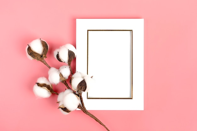 White photo frame and a sprig of cotton on a pink background Premium Photo