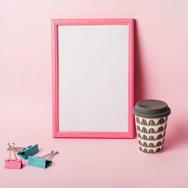 White picture frame with border; paper clips and coffee disposable cup against pink background Free Photo