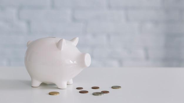 White piggybank and coins on desk Free Photo