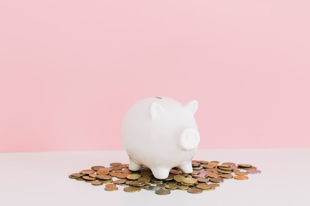 White piggybank over the coins on white table against pink background 23 2147892241