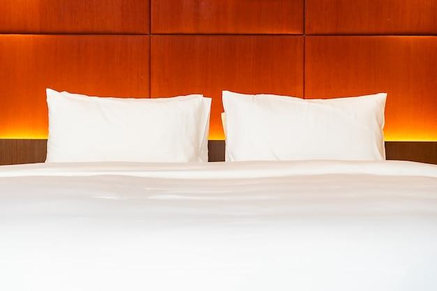 Белая подушка и одеяло на кровати с легкой лампой, украшающей интерьер спальни Бесплатные Фотографии