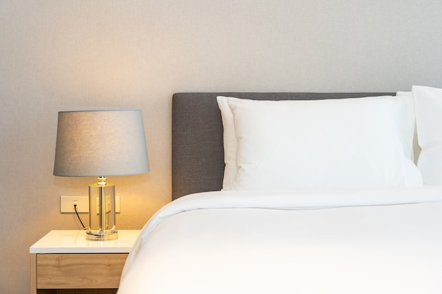 White pillow on bed with light lamp Free Photo