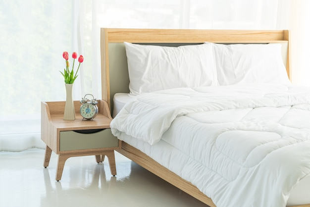 Белая подушка на кровати в спальне Premium Фотографии