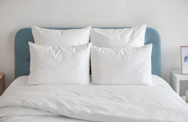 Белые подушки и пуховое одеяло на синей кровати. Premium Фотографии