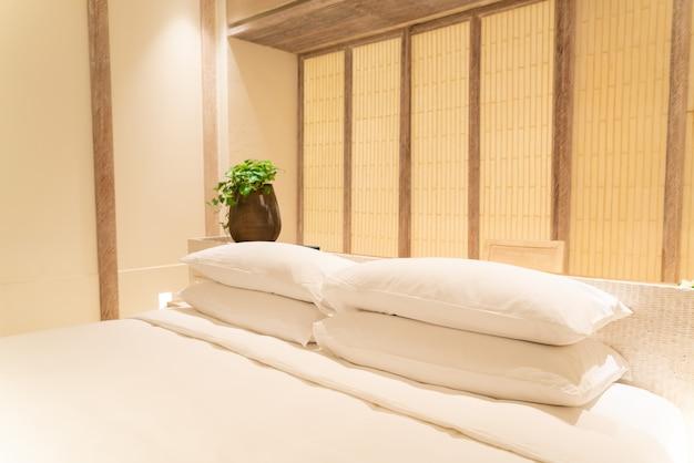 Украшение белыми подушками на кровати в роскошной спальне курортного отеля Premium Фотографии