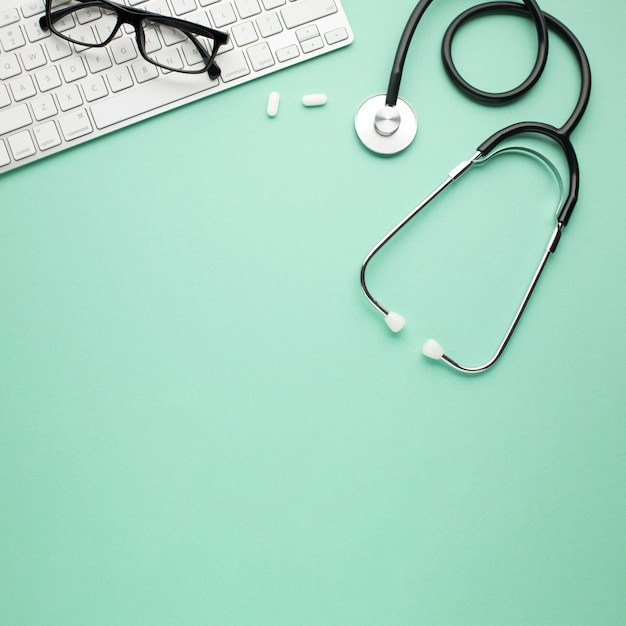 White pills and stethoscope near spectacles on wireless keyboard over backdrop Free Photo