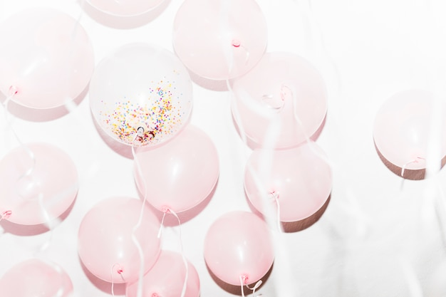 White and pink birthday balloons against white background Free Photo
