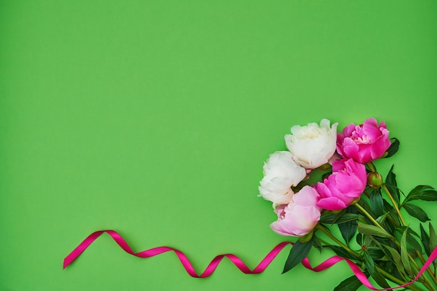 White and pink peonies decorated with pink ribbon on green background. holiday background, copyspace, top view Premium Photo