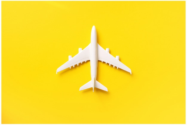 White plane, airplane on yellow color background with copy space. Premium Photo