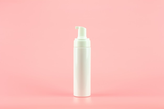 White plastic cosmetic lotion bottle on pink background. Premium Photo