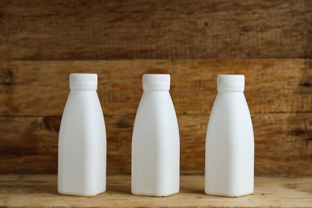 White plastic milk bottles on retro wooden table background 1387 786
