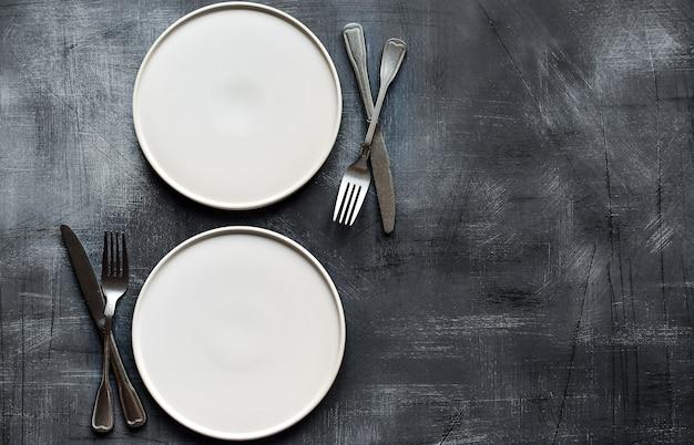 White plate on dark stone table. table setting. Premium Photo