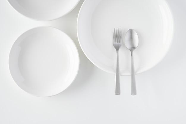 Белая тарелка, вилка, ложка Premium Фотографии