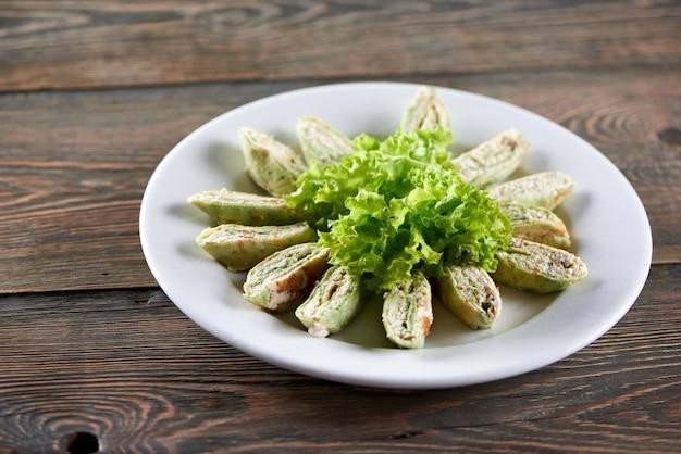 Белая тарелка, полная армянского лаваша с творогом и овощами. закуска украшена листьями салата. фото сделано на деревянном столе Бесплатные Фотографии