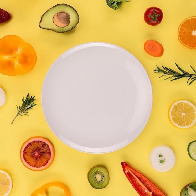 Белая тарелка в окружении овощей и фруктов Бесплатные Фотографии
