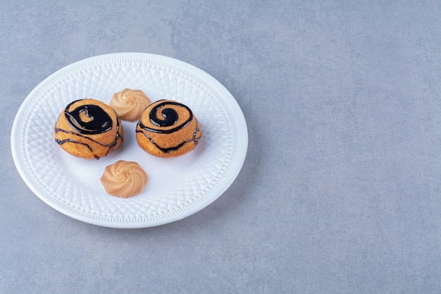 Un piatto bianco di deliziosi biscotti dolci con sciroppo di cioccolato. Foto Gratuite