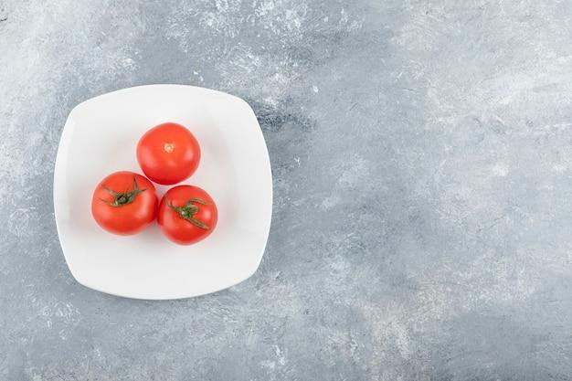 Un piatto bianco di tre pomodori rossi freschi su una priorità bassa di pietra. Foto Gratuite