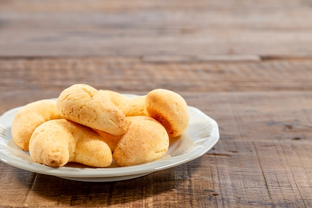White plate with cheese chipa, on top of a rustic wooden table in close up Premium Photo