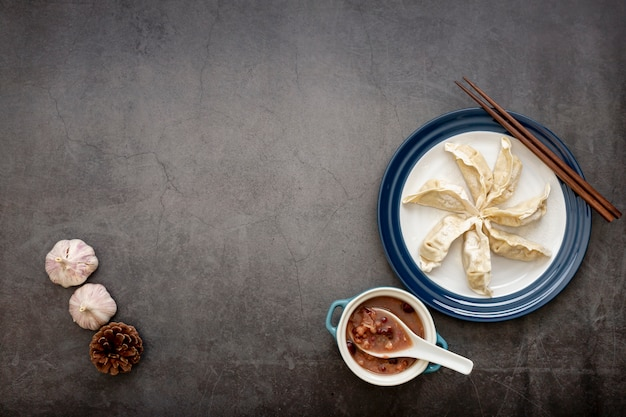 White plate with dim sum and garlic on a grey background Free Photo