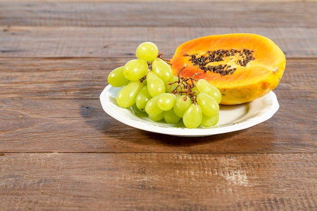 White plate with fruits: papaya and grape, on a rustic wooden table Premium Photo