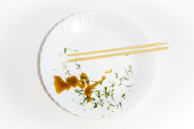 食べ残しと寿司箸、食べた食べ物、上面図の白いプレート Premium写真