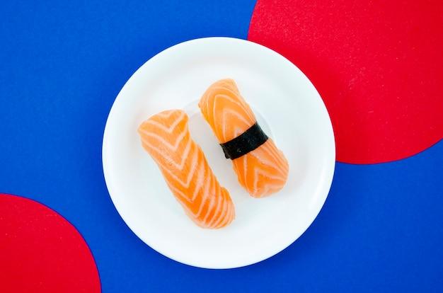 Белая тарелка с лососем суши на синем и красном фоне Бесплатные Фотографии