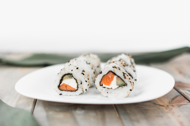 White plate with sushi on wooden table Free Photo