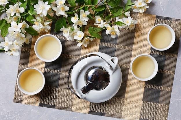 White porcelain asian tea set with green tea and jasmine on  bamboo napkin, top view. Premium Photo
