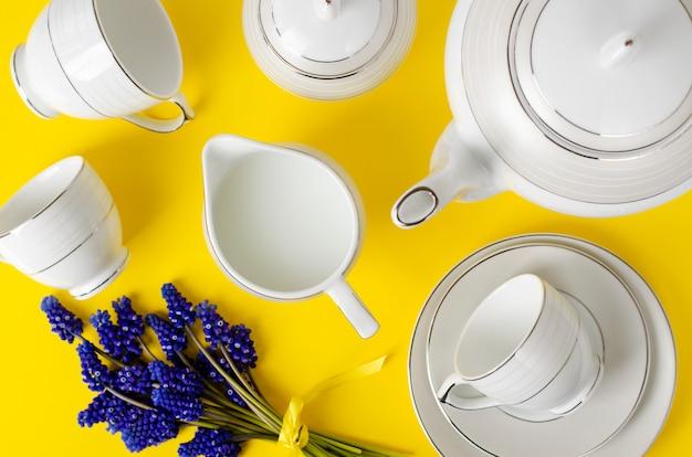 White porcelain coffe or tea set with muscari flowers on yellow Premium Photo