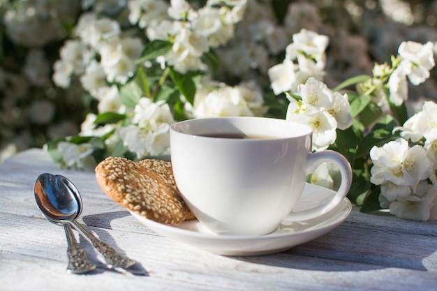 咲くジャスミンを背景に木製のテーブルに紅茶とゴマと2つのオートミールクッキーと白磁カップ。 Premium写真