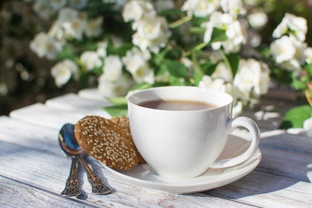 Белая фарфоровая чашка с чаем и двумя овсяным печеньем с кунжутом на деревянном столе на фоне цветущего жасмина. Premium Фотографии