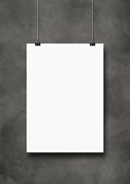 White poster hanging on a dark concrete wall with clips Premium Photo