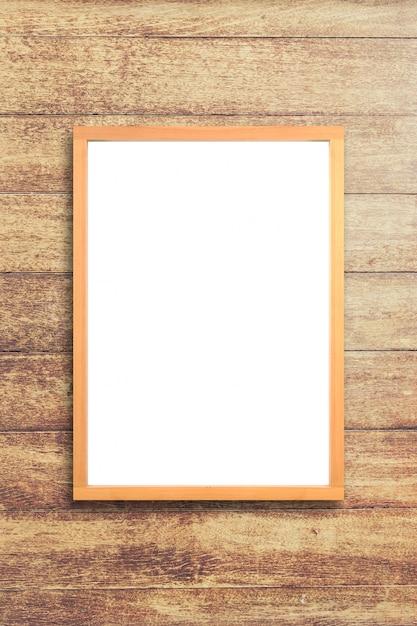 木製の壁の背景に木製のフレーム模造を持つ白いポスター。モックアップ。 Premium写真