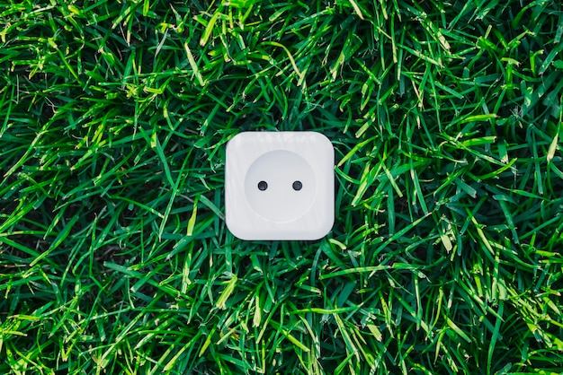 White power outlet on green grass Free Photo