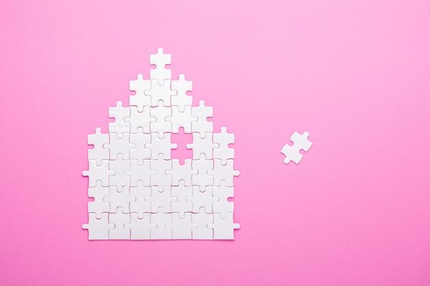 White puzzle. house shape puzzle. the concept of rent, mortgage. top view Premium Photo