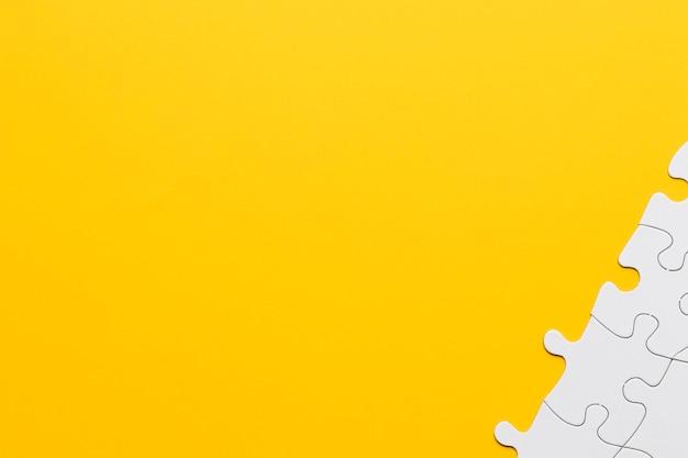 黄色の背景の隅に白いパズルのピース 無料写真
