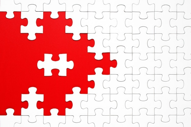 White puzzle pieces on a red background separated Premium Photo