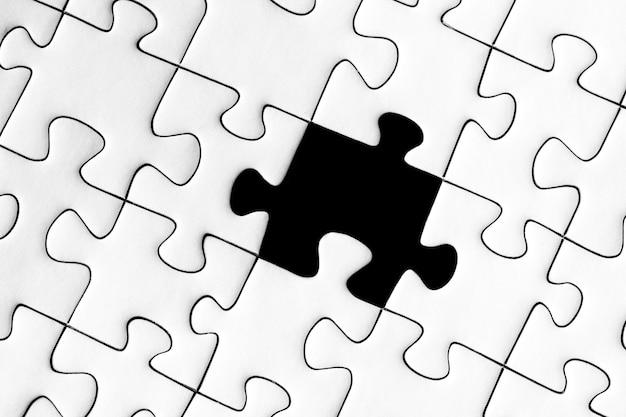 Puzzle bianco con un pezzo nero mancante: completa il concetto di missione Foto Gratuite