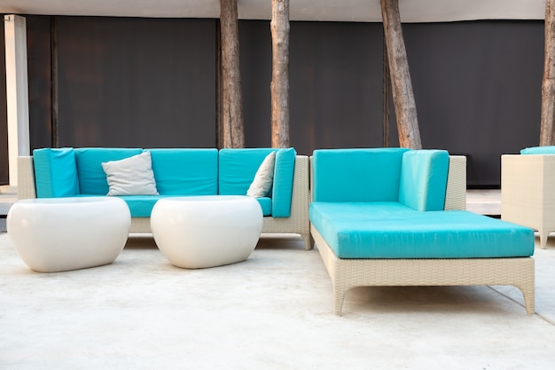 White rattan garden furniture with blue cushion on resort terrace. Premium Photo