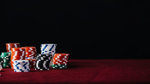White; red; black and green casino chip stack on red poker table Premium Photo