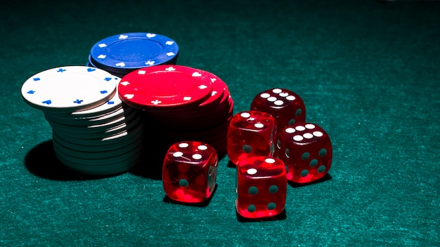 White; red and blue casino chip stack with red dices on green background Free Photo