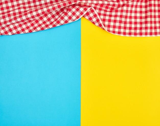 White red checkered kitchen towel on a blue yellow background Premium Photo