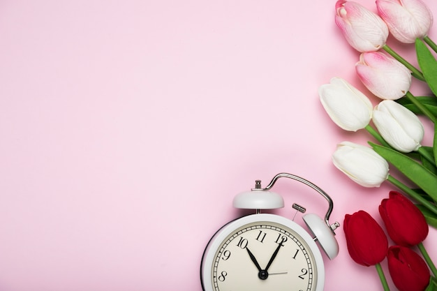 White and red tulips beside clock with copy-space Free Photo