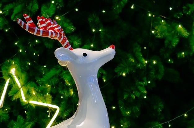 Белый олень с красным рогом стоит перед елкой с огнями Premium Фотографии