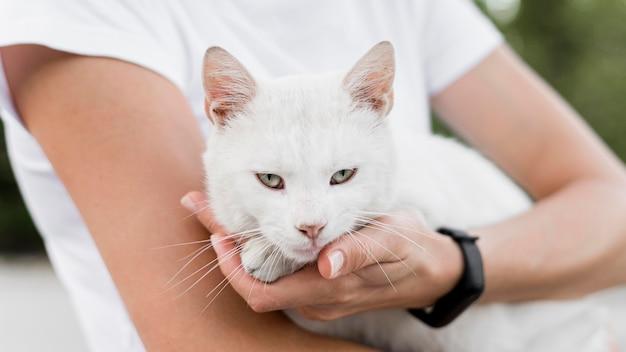 Женщина держит белого кота-спасателя в приюте для усыновителей Бесплатные Фотографии