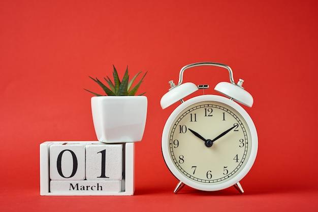 赤い背景と木製のカレンダーブロックに白いレトロな目覚まし時計 Premium写真