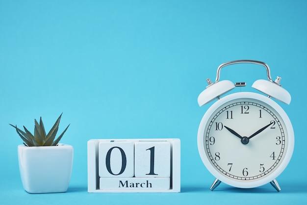 青い背景に鐘と木製のカレンダーブロックと白いレトロな目覚まし時計 Premium写真